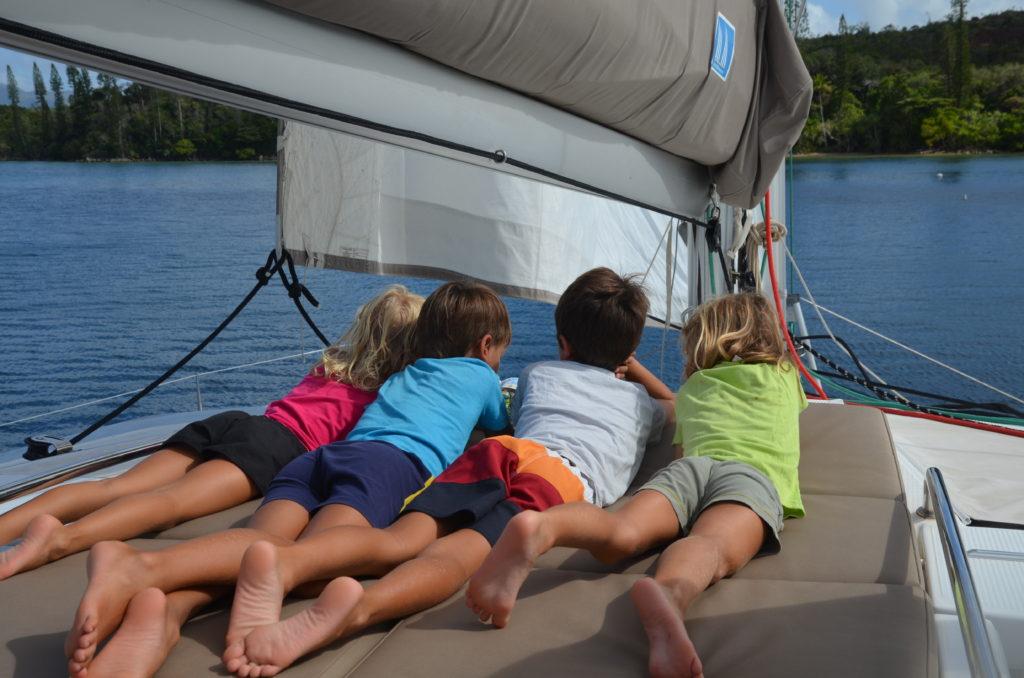 Enfants sur le sundeck du catamaran abaca regardant le lagon et ses ilots
